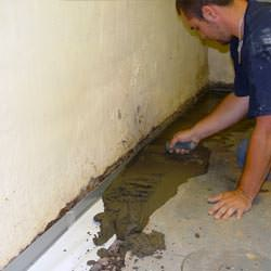 A basement waterproofer installing a perimeter drain system in Ladysmith